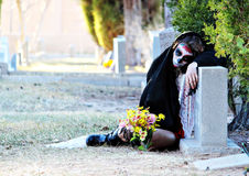 Dia De Los Muertos - Sorrow. Sad woman in Dia De Los Muertos, Day of the Dead, makeup leaning on headstone with flowers Stock Images