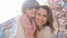 Dia de matrizes Duas mulheres bonitas são fotografadas contra o céu brilhante da mola e uma magnólia e um sakura de florescência filme