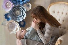 Dia de matrizes feliz Mulher feliz adorável com o bebê que levanta em decorações modernas à moda do estúdio Elemento do projeto p foto de stock royalty free