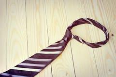 Dia de pais feliz com a gravata listrada vermelha, cinzenta e preta no fundo da madeira de pinho no estilo do vintage Imagem de Stock