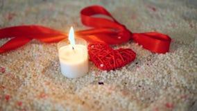 Dia de são valentim da decoração com queimadura da vela e fita na areia filme
