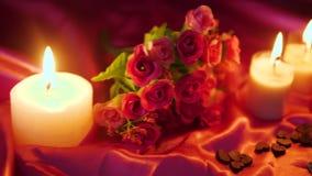 Dia de são valentim da metragem da decoração com queimadura da vela e ramalhete da flor filme