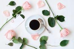 Dia de são valentim do St - a xícara de café, as rosas do pêssego, o cartão vazio do amor e o coração deram forma a doces, fundo  Foto de Stock