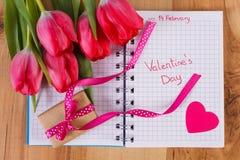 Dia de Valentim escrito no caderno, nas tulipas frescas, no presente envolvido e no coração, decoração para Valentim Imagem de Stock
