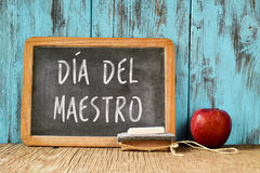 Dia del maestro, teachers day in Spanish. A chalkboard with the text dia del maestro, teachers day written in Spanish, a piece of chalk, an eraser and a red Stock Photography
