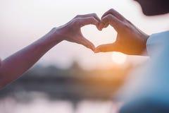 Dia do amor da mão nova com o coração de dois povos Imagens de Stock Royalty Free