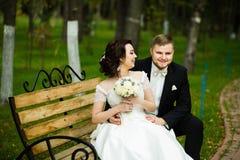 Dia do casamento: os noivos bonitos sentam-se no banco no parque Foto de Stock