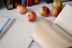 Dia do conhecimento Abra o livro, o caderno, a pena e maçãs vermelhas maduras em t Fotografia de Stock Royalty Free