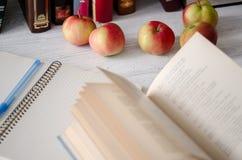 Dia do conhecimento Abra o livro, o caderno, a pena e maçãs vermelhas maduras em t Fotografia de Stock