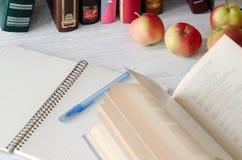 Dia do conhecimento Abra o livro, o caderno, a pena e maçãs vermelhas maduras em t Imagens de Stock Royalty Free