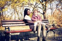 Dia do outono Mãe e filha que sentam-se no banco imagens de stock royalty free