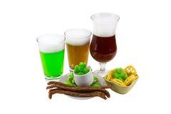 Dia do ` s de Patrick - três vidros da cerveja de malte não filtrada de bambu da cerveja com uma variedade de petiscos e trevo do Fotos de Stock