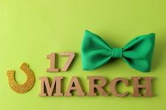 Dia do ` s de StPatrick celebration Laço e ferradura e texto verdes o 17 de março em um fundo verde-claro Vista de acima imagens de stock royalty free