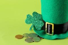Dia do ` s de StPatrick celebration O chapéu de um duende, de moedas e de uma folha do trevo é um modelo em um fundo verde-claro imagens de stock royalty free