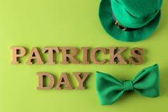 Dia do ` s de StPatrick celebration Um laço verde, um chapéu do duende e o texto do 17 de março em um fundo verde-claro a parte s imagens de stock