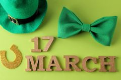 Dia do ` s de StPatrick celebration Um laço verde, um chapéu do duende e uma ferradura e o texto do 17 de março em uma parte tras foto de stock