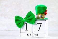 Dia do ` s de StPatrick Um calendário de madeira que mostra o 17 de março Chapéu e curva verdes Fotos de Stock