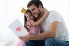 Dia do `s do pai Filha feliz da família que dá a paizinho um cartão no feriado fotos de stock royalty free