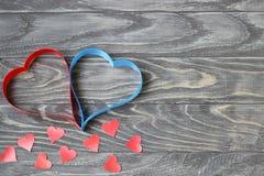 Dia do `s do Valentim Dois corações das fitas de vermelho e de azul em um CCB Imagem de Stock