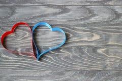 Dia do `s do Valentim Dois corações das fitas de vermelho e de azul em um CCB Imagens de Stock