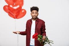 Dia do ` s do Valentim: Homem afro-americano que guarda a rosa e o balão do vermelho com expressão desapontado fotos de stock royalty free