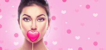 Dia do `s do Valentim A menina nova do modelo de forma da beleza com coração do Valentim deu forma à cookie sobre o rosa fotografia de stock royalty free