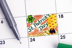 Dia do St Patricks do lembrete no calendário com pena verde Imagem de Stock