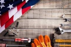 Dia do Trabalhador, bandeira dos EUA Am?rica com muitas ferramentas acess?veis na textura de madeira do fundo imagens de stock