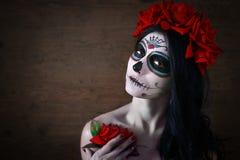 Dia dos mortos Halloween A jovem mulher no dia da arte inoperante da cara do crânio da máscara e aumentou Fundo escuro fotografia de stock royalty free