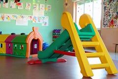 Dia en plastic tunnel in de speelkamer van een kleuterschool Stock Afbeeldingen