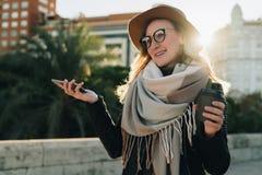 Dia ensolarado do outono, luminoso O turista atrativo novo da mulher no chapéu, monóculos e com trouxa está na rua da cidade Imagens de Stock