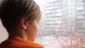 Dia ensolarado do ` s do inverno Um indivíduo novo está ao lado da janela e olha a neve de queda vídeos de arquivo