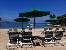 Dia ensolarado e relaxamento na praia que senta-se na cadeira de plataforma fotografia de stock