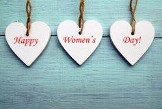 Dia feliz do ` s das mulheres Corações de madeira brancos decorativos em um fundo de madeira rústico azul fotografia de stock royalty free
