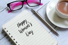 Dia feliz do ` s das mulheres escrito no caderno Imagem de Stock