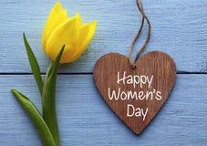 Dia feliz do ` s das mulheres Tulipa amarela e coração de madeira decorativo no fundo de madeira azul Fotos de Stock