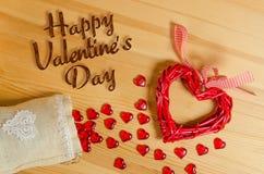 Dia feliz do ` s do Valentim do sinal do coração em uma textura de madeira, e derramamento fora do saco com corações de vidro peq Imagens de Stock