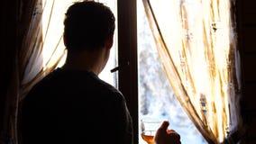 Dia gelado do inverno O indivíduo cedo na posição da manhã na janela e no chá quente bebendo vídeos de arquivo