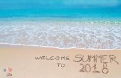 Dia il benvenuto a all'estate 2018 scritta su una spiaggia tropicale fotografia stock