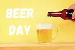 Dia internacional da cerveja Um homem derrama a cerveja em uma caneca de um bottl fotografia de stock royalty free