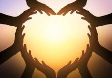 Dia internacional do conceito da amizade: mãos na forma do coração no fundo borrado fotos de stock