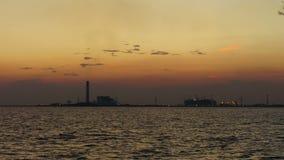 dia 4K ao Noite-lapso: Fábrica da refinaria de petróleo na silhueta e no céu do mar do por do sol, Tailândia vídeos de arquivo