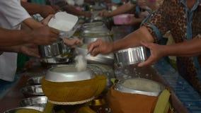 Dia le elemosine di riso ad un monaco buddista in tempio video d archivio