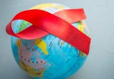 Dia Mundial do Sida o 1º de dezembro, close-up do globo do mundo com fita vermelha imagem de stock