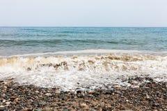 Dia nebuloso no lado da praia com as ondas que batem o litoral Espuma do mar nas ondas Praia rochosa com pedras coloridas Withou  foto de stock royalty free