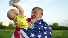 Dia patri?tico O av? e o neto pequeno comemoram o Dia da Independ?ncia dos E.U. A crian?a remove seu tamp?o do seu video estoque