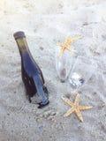 Dia romântico com os vidros do vinho tinto que sentam-se na praia Fotos de Stock