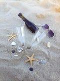 Dia romântico com os vidros do vinho tinto que sentam-se na praia Imagens de Stock Royalty Free
