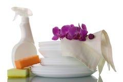 Dia von sauberen Platten, von Abwaschflüssigkeit, von Schwämmen und von Serviette auf Weiß Stockbild