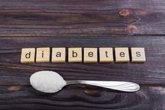 Sugar pile on a spoon and diabetes block wooden letters Stock Image